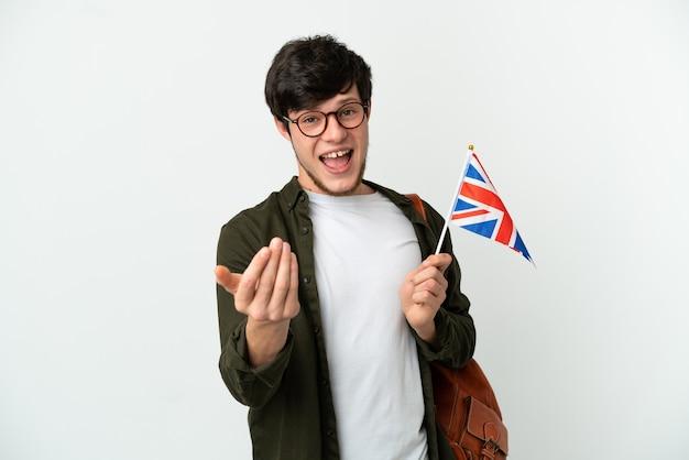 Giovane uomo russo in possesso di una bandiera del regno unito isolata su sfondo bianco che invita a venire con la mano. felice che tu sia venuto