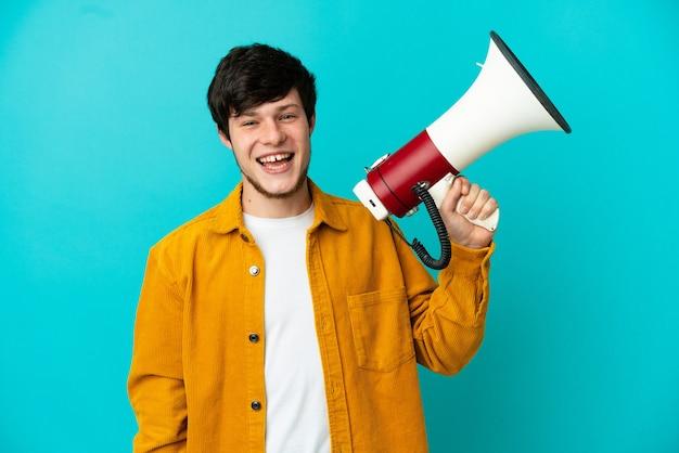 Giovane uomo russo isolato su sfondo blu in possesso di un megafono e sorridente