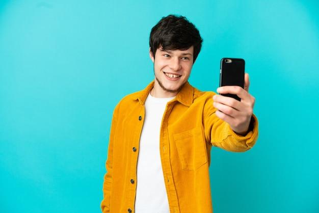 Giovane uomo russo isolato su sfondo blu facendo un selfie con il cellulare