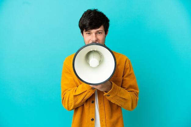 Giovane uomo russo isolato su sfondo blu che grida attraverso un megafono per annunciare qualcosa