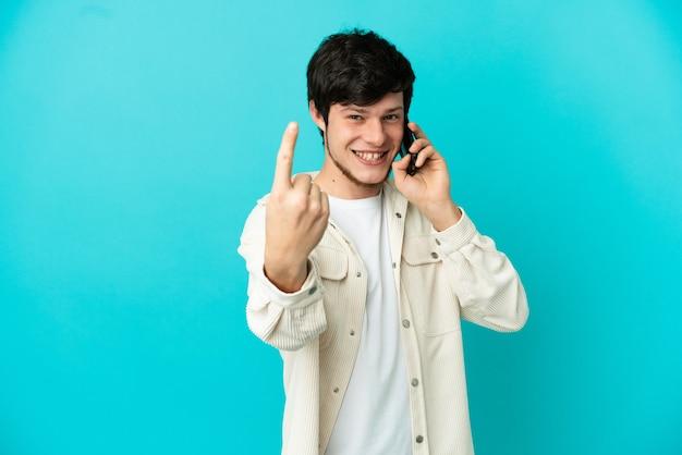 Giovane uomo russo che usa il telefono cellulare isolato su sfondo blu facendo un gesto imminente