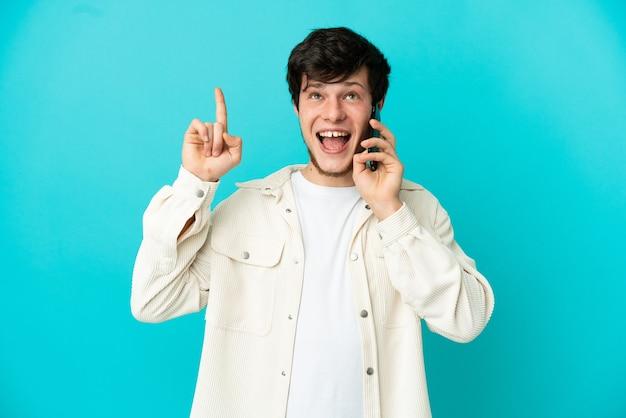 Giovane uomo russo che utilizza il telefono cellulare isolato su sfondo blu che indica una grande idea