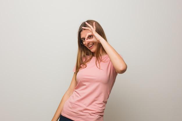 Giovane ragazza naturale russa fiduciosa che fa gesto giusto sull'occhio
