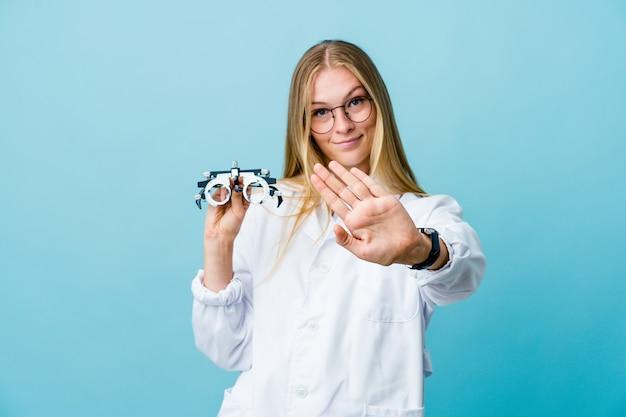 Giovane donna russa dell'ottico optometrista sull'azzurro che fa un gesto di diniego