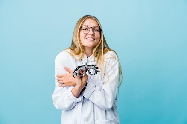 Giovane donna all'ottico optometrista russo sul blu che va freddo a causa della bassa temperatura o di una malattia.