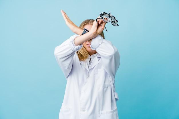 Giovane donna all'ottico optometrista russo sul blu mantenendo due braccia incrociate, concetto di negazione.