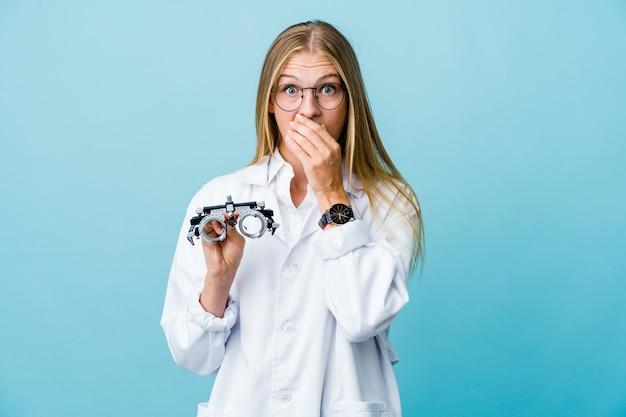 Giovane donna all'ottico optometrista russo sulla bocca della copertura scioccata blu con le mani.