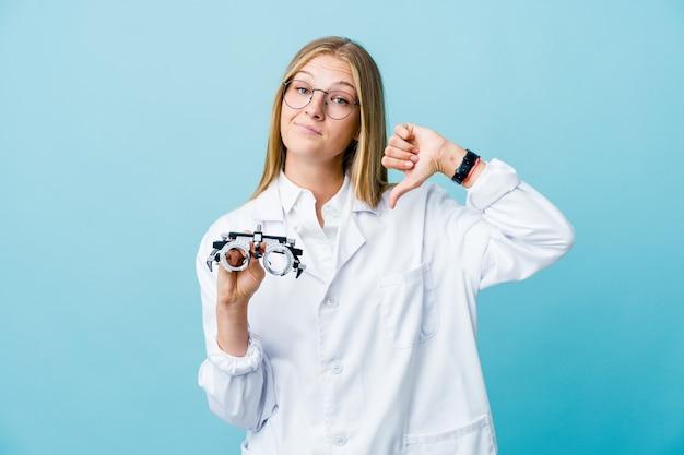 Giovane donna russa all'ottico optometrista sull'azzurro che mostra un gesto di antipatia, i pollici verso il basso. concetto di disaccordo.