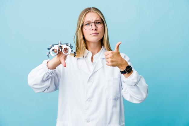 Giovane donna all'ottico optometrista russo sul blu che mostra i pollici in su e in giù, difficile scegliere il concetto