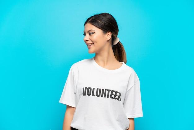 Giovane ragazza volontaria russa isolata su sfondo blu che guarda di lato