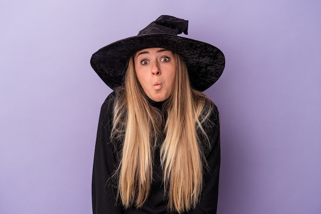 La giovane donna russa travestita da strega che celebra halloween isolata su sfondo viola alza le spalle e apre gli occhi confusi.