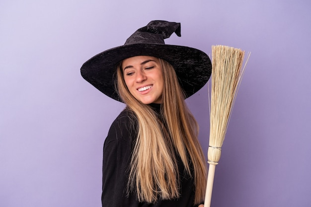 La giovane donna russa travestita da strega con in mano una scopa isolata su sfondo viola sembra da parte sorridente, allegra e piacevole.