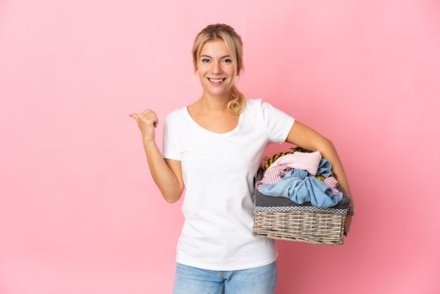 Giovane donna russa che tiene un cesto di vestiti isolato su sfondo rosa che punta al lato per presentare un prodotto