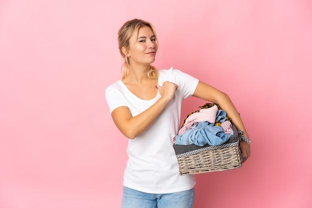 Giovane donna russa che tiene un cesto di vestiti isolato su sfondo rosa orgoglioso e soddisfatto di sé