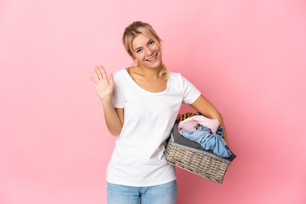 Giovane donna russa che tiene un cesto di vestiti isolato su sfondo rosa salutando con la mano con espressione felice