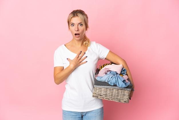 Giovane donna russa che tiene un cesto di vestiti isolato su sfondo rosa sorpreso e scioccato mentre guarda a destra