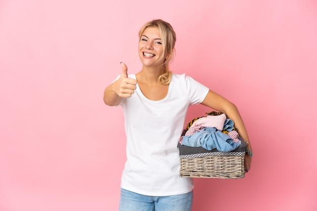 Giovane donna russa in possesso di un cesto di vestiti isolato su sfondo rosa con il pollice in alto perché è successo qualcosa di buono