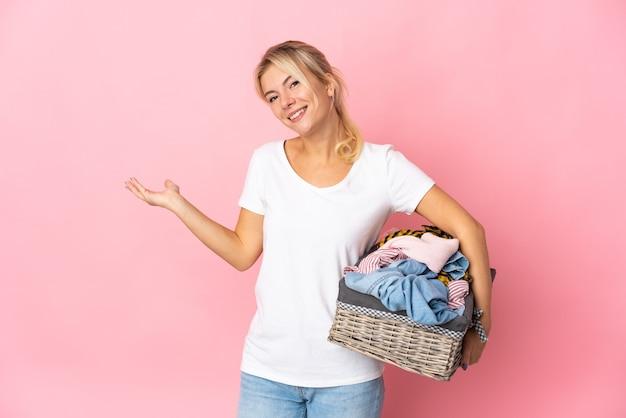 Giovane donna russa che tiene un cesto di vestiti isolato sulla parete rosa che estende le mani a lato per invitare a venire