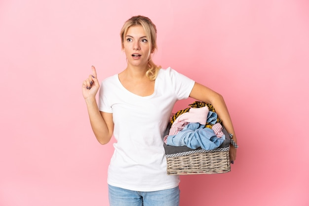 Giovane donna russa che tiene un cesto di vestiti isolato sul muro rosa pensando un'idea puntando il dito verso l'alto
