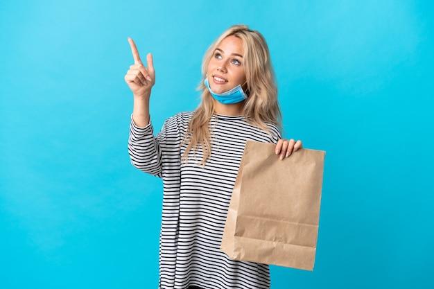 Giovane donna russa in possesso di un sacchetto della spesa isolato su sfondo blu che punta con il dito indice una grande idea