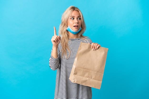 Giovane donna russa che tiene una borsa della spesa isolata sull'azzurro che intende realizzare la soluzione mentre solleva un dito
