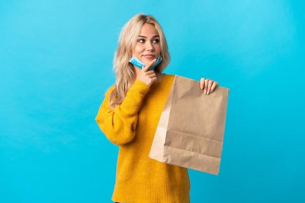 Giovane donna russa che tiene una borsa della spesa isolata sull'azzurro che pensa un'idea mentre osserva in su