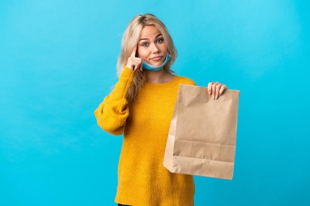 Giovane donna russa che tiene una borsa della spesa isolata sull'azzurro che pensa un'idea