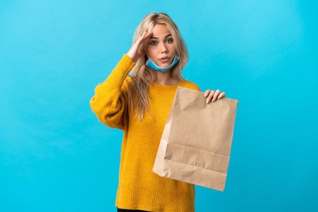 La giovane donna russa che tiene un sacchetto della spesa isolato sulla parete blu ha realizzato qualcosa e intende la soluzione