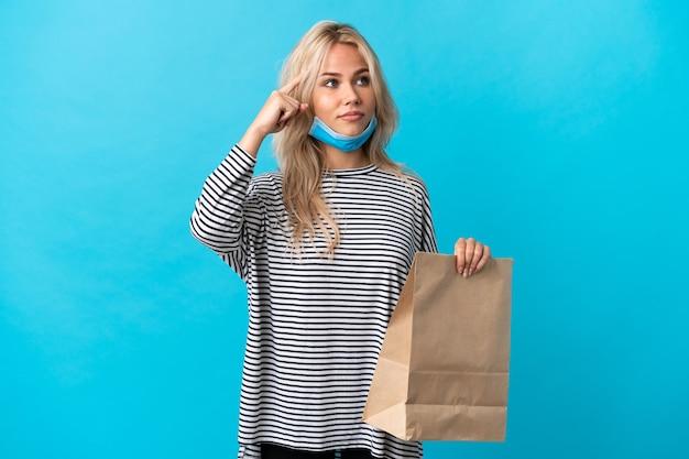 Giovane donna russa che tiene un sacchetto della spesa isolato sulla parete blu avendo dubbi e pensando