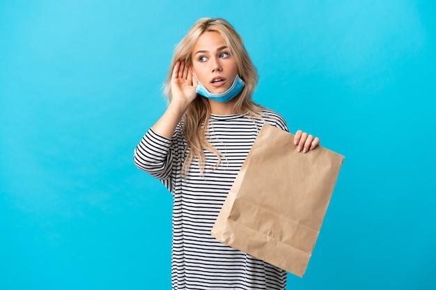 Giovane donna russa che tiene una borsa della spesa isolata sulla parete blu che ascolta qualcosa mettendo la mano sull'orecchio