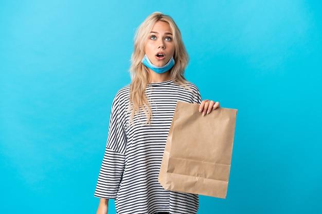 Giovane donna russa che tiene un sacchetto della spesa della drogheria isolato sulla parete blu che osserva in su e con l'espressione sorpresa