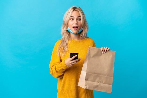 Giovane donna russa che tiene un sacchetto della spesa isolato sulla parete blu sorpresa e l'invio di un messaggio