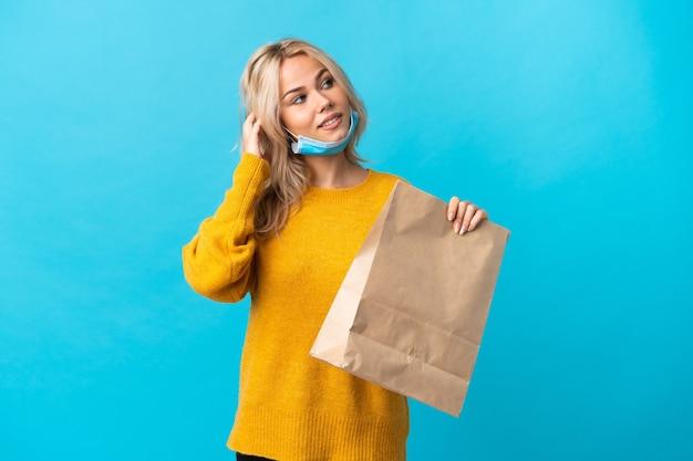 Giovane donna russa che tiene una borsa della spesa isolata sulla parete blu che pensa un'idea