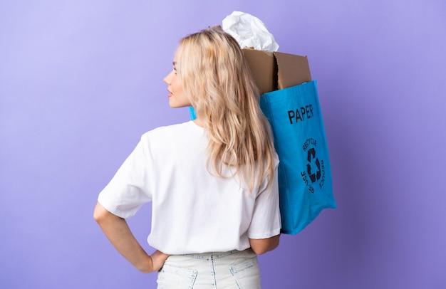 Giovane donna russa in possesso di un sacchetto di riciclaggio pieno di carta da riciclare isolato su viola in posizione posteriore e guardando il lato