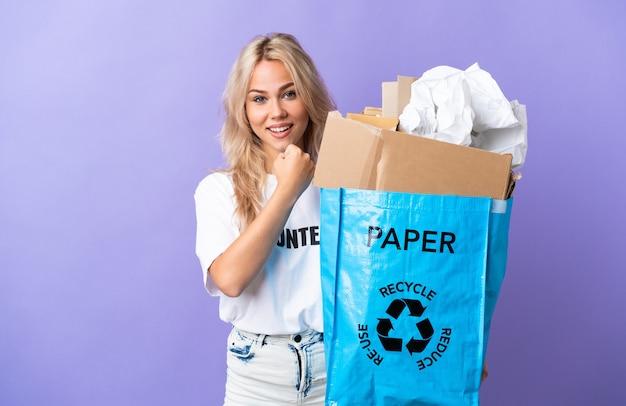 Giovane donna russa che tiene un sacchetto di riciclaggio pieno di carta da riciclare isolato su viola che celebra una vittoria