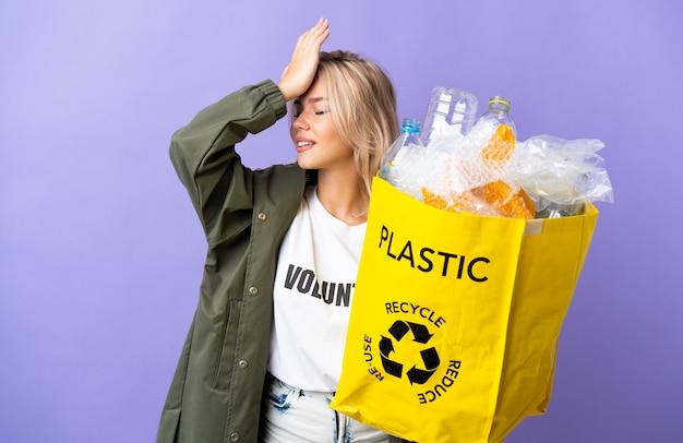 La giovane donna russa che tiene un sacchetto di riciclaggio pieno di carta per riciclare isolato su viola ha realizzato qualcosa e intende la soluzione