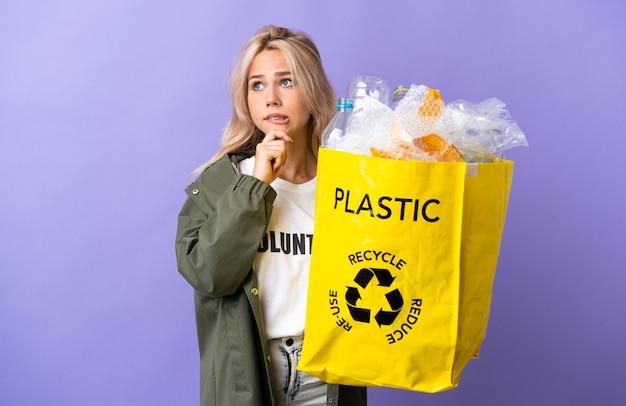 Giovane donna russa che tiene un sacchetto di riciclaggio pieno di carta da riciclare isolato su viola avendo dubbi e pensiero