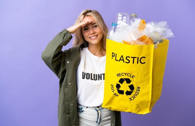 Giovane donna russa che tiene un sacchetto di riciclaggio pieno di carta da riciclare isolato su viola che guarda lontano con la mano per guardare qualcosa