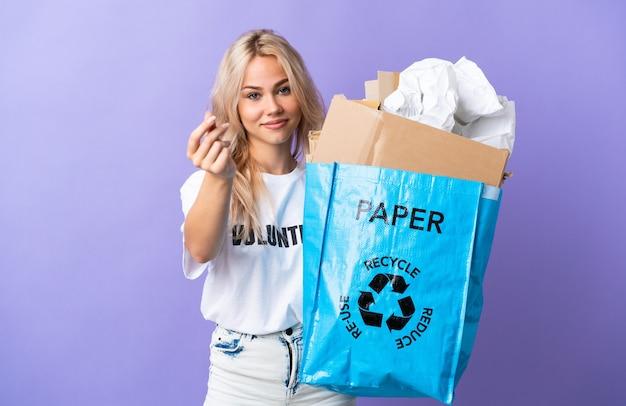 Giovane donna russa che tiene un sacchetto di riciclaggio pieno di carta da riciclare isolato sul gesto di fare soldi viola