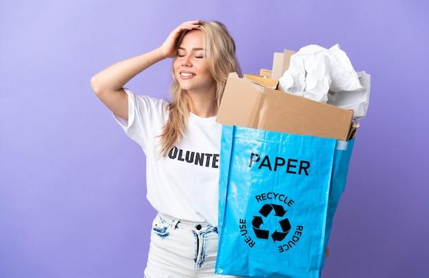 Giovane donna russa in possesso di un sacchetto di riciclaggio pieno di carta da riciclare isolato su viola sorridente molto