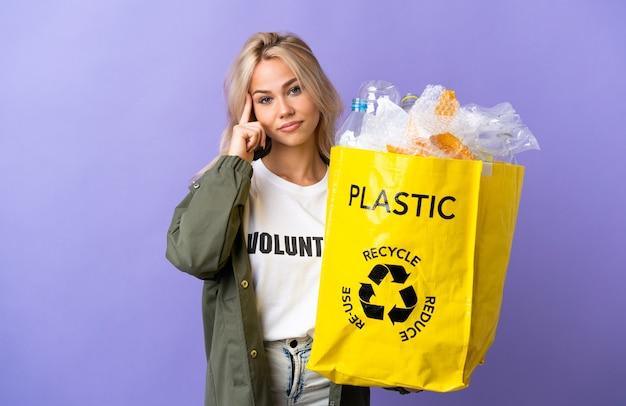 Giovane donna russa che tiene un sacchetto di riciclaggio pieno di carta da riciclare isolato sul muro viola pensando un'idea