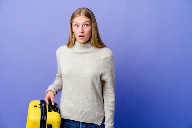 Giovane donna russa che tiene la valigia per viaggiare scioccata a causa di qualcosa che ha visto.