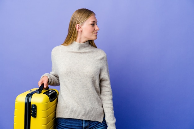 Giovane donna russa che tiene la valigia per viaggiare guardando a sinistra, posa lateralmente.