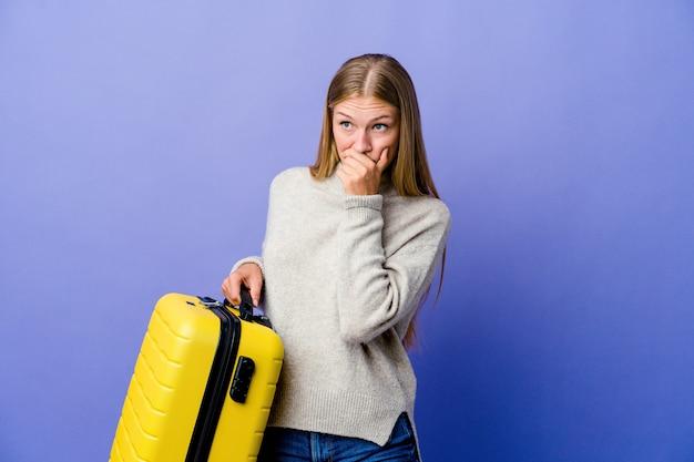 Giovane donna russa che tiene la valigia per viaggiare premuroso alla ricerca di uno spazio di copia che copre la bocca con la mano.