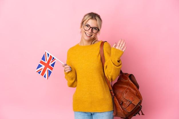Giovane donna russa che tiene una bandiera del regno unito isolata su sfondo rosa salutando con la mano con l'espressione felice