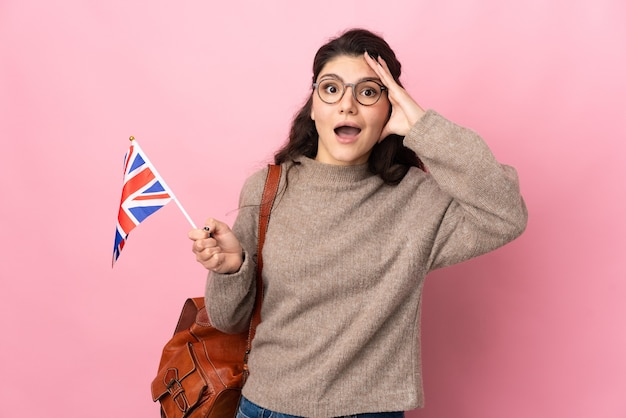 Giovane donna russa in possesso di una bandiera del regno unito isolata su sfondo rosa con espressione di sorpresa