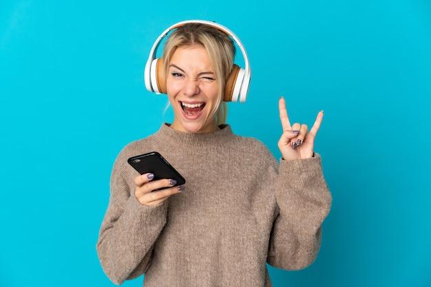 Giovane donna russa isolata su sfondo blu ascoltando musica con un cellulare che fa gesto rock