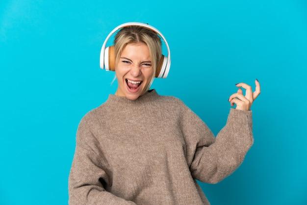 Giovane donna russa isolata sulla parete blu che ascolta musica e che fa il gesto della chitarra