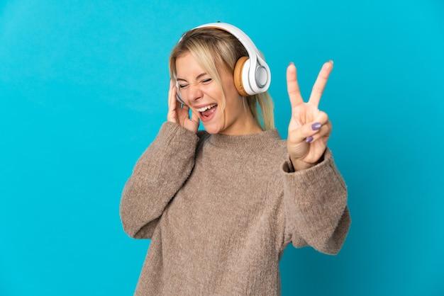 Giovane donna russa isolata sulla parete blu che ascolta musica e canto