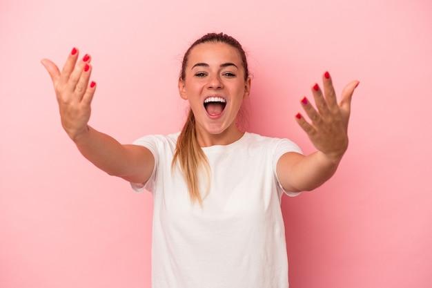 Giovane donna russa isolata su sfondo rosa che celebra una vittoria o un successo, è sorpreso e scioccato.